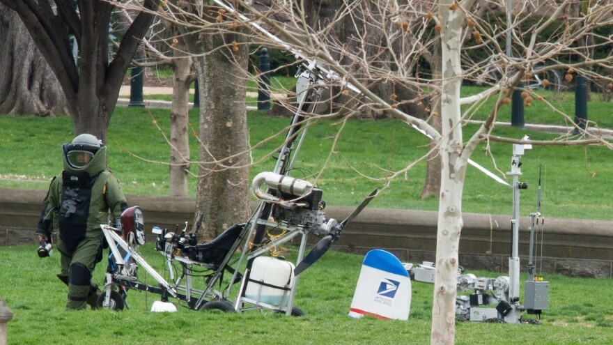 An Explosive Ordnance Disposal Technician and a robotic police device check Hughes' gyrocopter after it on the South Lawn of the Capitol.