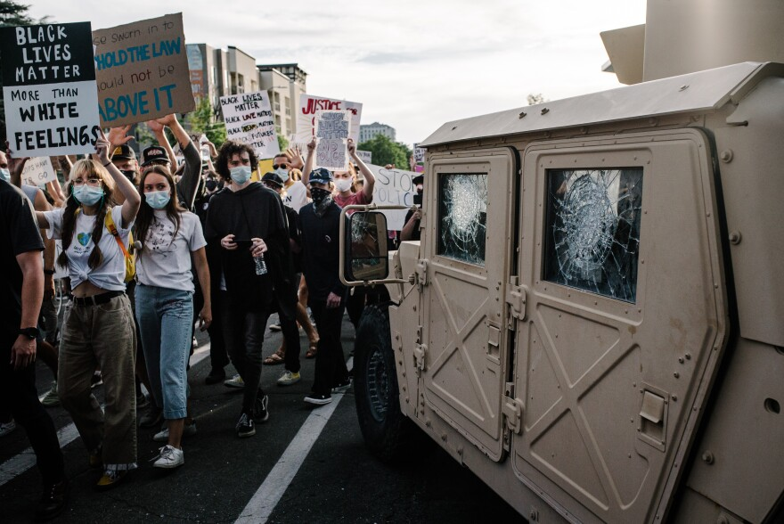 """Photo of a tan Hummer with spidered windows and a crowd of people filing past with signs that say things like """"Black lives matter more than white feelings."""""""