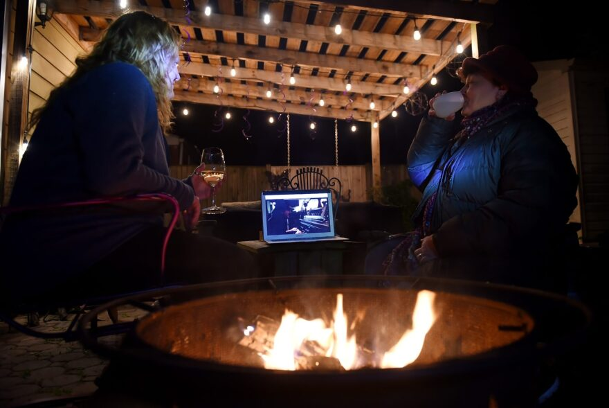 """Neighbors sit around a fire-pit to watch Eddie Vedder perform during the """"One World: Together at Home"""" concert in a backyard in Arlington, Virginia."""