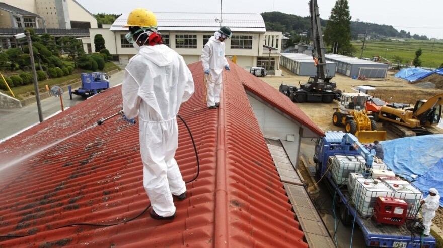 Workers decontaminate the roof of a kindergarten about 12 miles from the crippled Fukushima nuclear plant in Japan last month. Several hundred Japanese seniors have volunteered to take part in the cleanup effort.