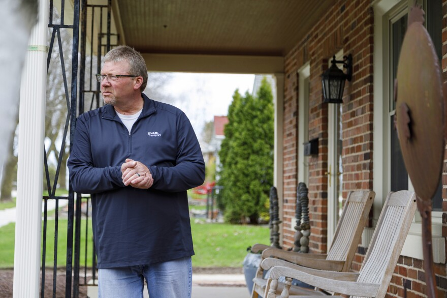 George Cooper, a truck driver for Kohler, stands on the front porch of his home. When he started his job at Kohler two years ago, Cooper realized his pay and benefits were no match to those of other drivers doing the same work.