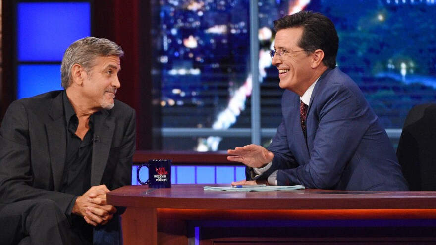 New <em>Late Show</em> host Stephen Colbert (right) talks with actor George Clooney.