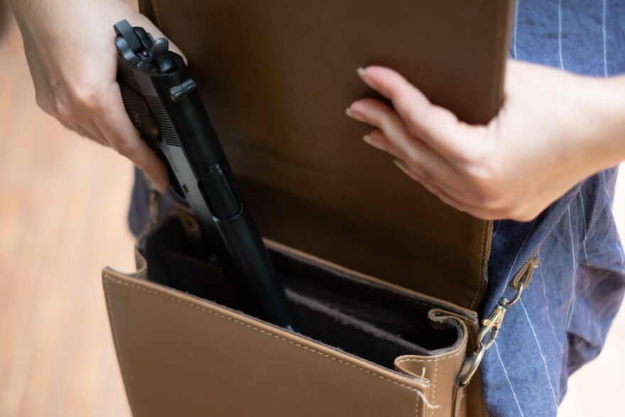 A photo of a woman putting a gun into her purse.