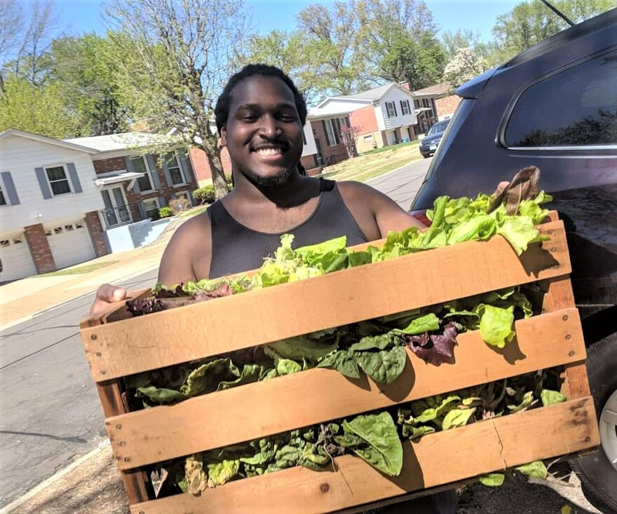 Eric Wiliams carries a crate of lettuce from the community garden at local nonprofit A Red Circle. The nonprofit is starting a farmers market in Riverview.