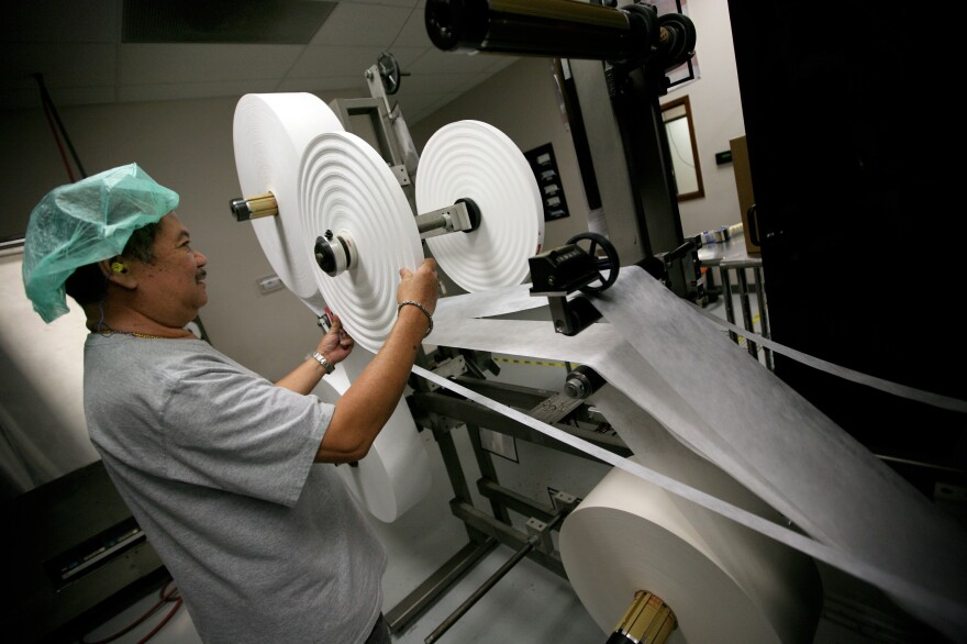 Prestige Ameritech employee Saengdara Phanvilay, pictured during the 2009 swine flu outbreak, inspects a machine that produces disposable surgical masks.