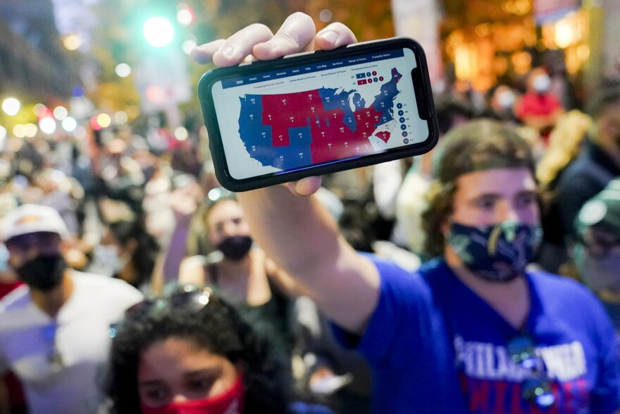 A supporter of President-elect Joe Biden holds up a phone displaying the Electoral College map in Philadelphia on Nov. 7.