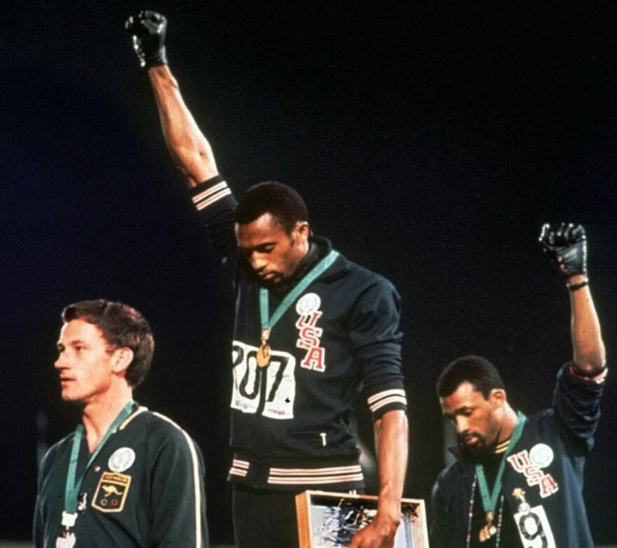 Australian silver medalist Peter Norman (left) stands on the podium as Americans Tommie Smith (center) and John Carlos raise their gloved fists in a human rights protest at the 1968 Summer Olympics in Mexico City.