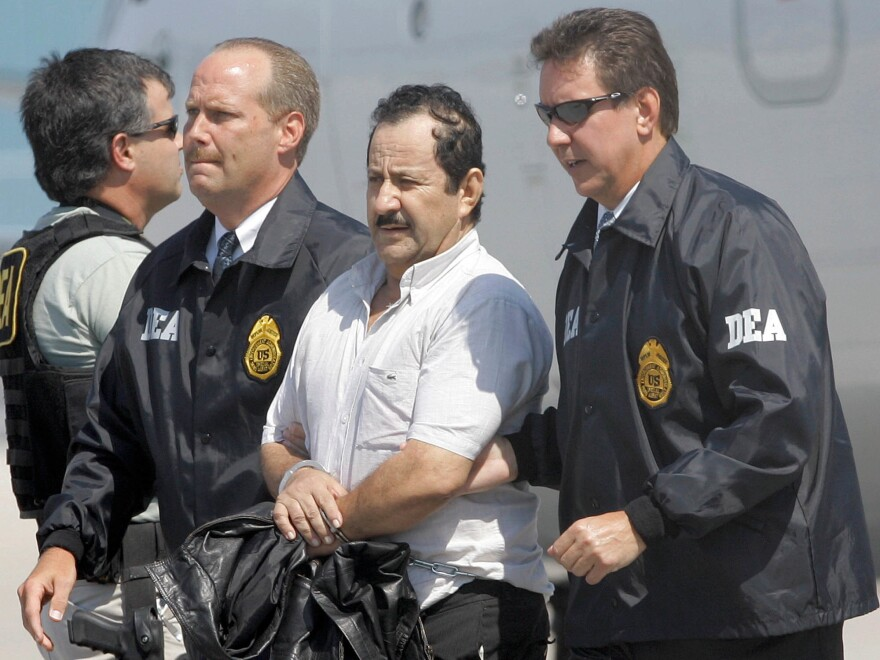 Colombian paramilitary Hernan Giraldo Serna, second right, is escorted by U.S. DEA Agents at his arrival in Opa-locka, Fla., on May 13, 2008. Members of a Colombian paramilitary group arrived from Colombia to face U.S. drug trafficking and money laundering charges in federal court.