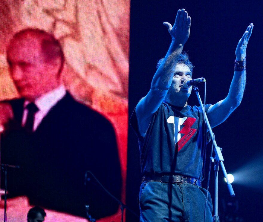 "The Russian pop group Televizor has criticized Russia's involvement in Ukraine. Here, frontman Mikhail Borzykin performs at a 2011 show in St. Petersburg. At some concerts he sings, ""Putin is a fascist,"" a reference to the Russian president, shown on the screen behind him."