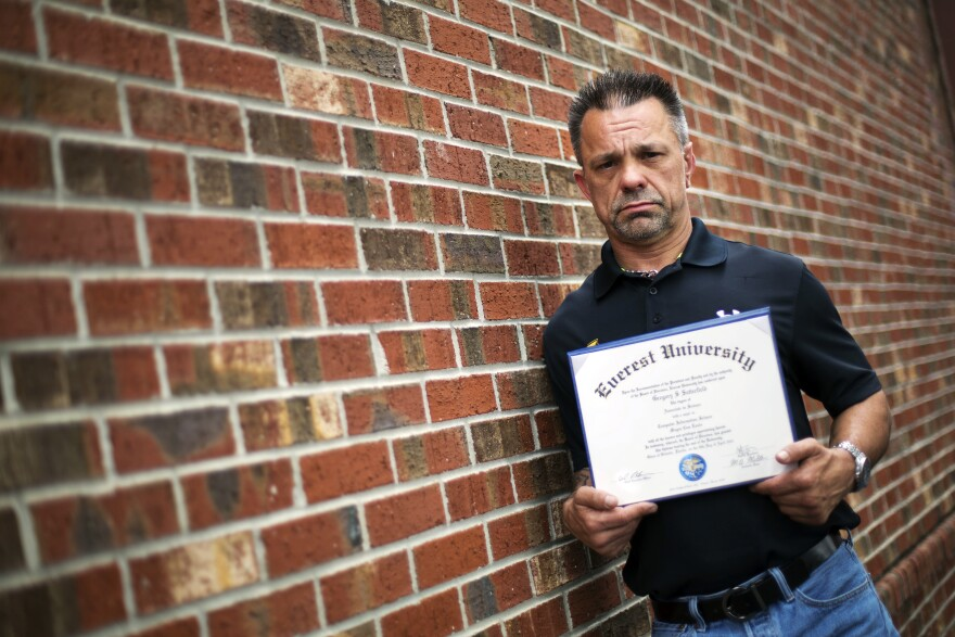 """Shane Satterfield, a roofer who owes more than $30,000 in debt for an associate's degree in computer science from one of the country's largest for-profit college companies that failed in 2014, holds his diploma in Atlanta. """"I graduated in April at the top of my class, with honors,"""" says Satterfield. """"And I can't get a job paying over $8.50 an hour."""""""