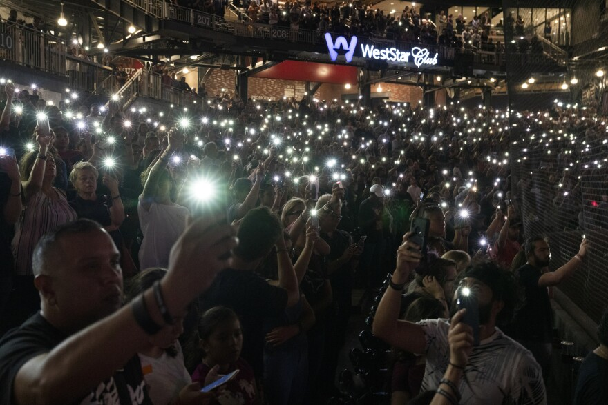 People raise their phone lights in the air while the names of the 22 victims of a recent mass shooting are read aloud during Wednesday night's memorial service.