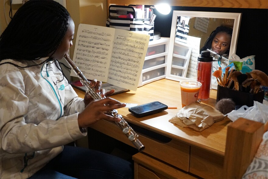 Ngone practices the flute inside her dorm room.