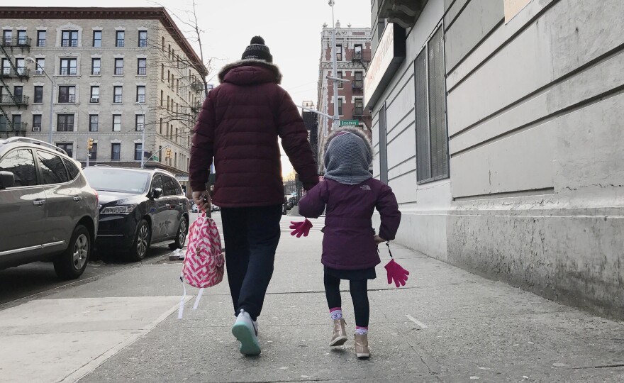 Eduardo walks with his daughter in New York City.