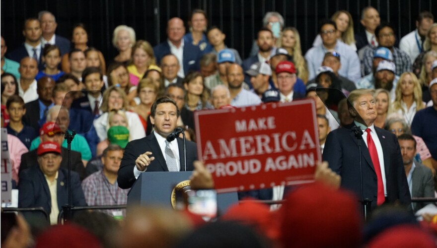 Then Rep. Ron DeSantis and President Donald Trump speak in front of a large crowd at a July 31, 2018 rally at the Florida State Fairgrounds in Tampa.