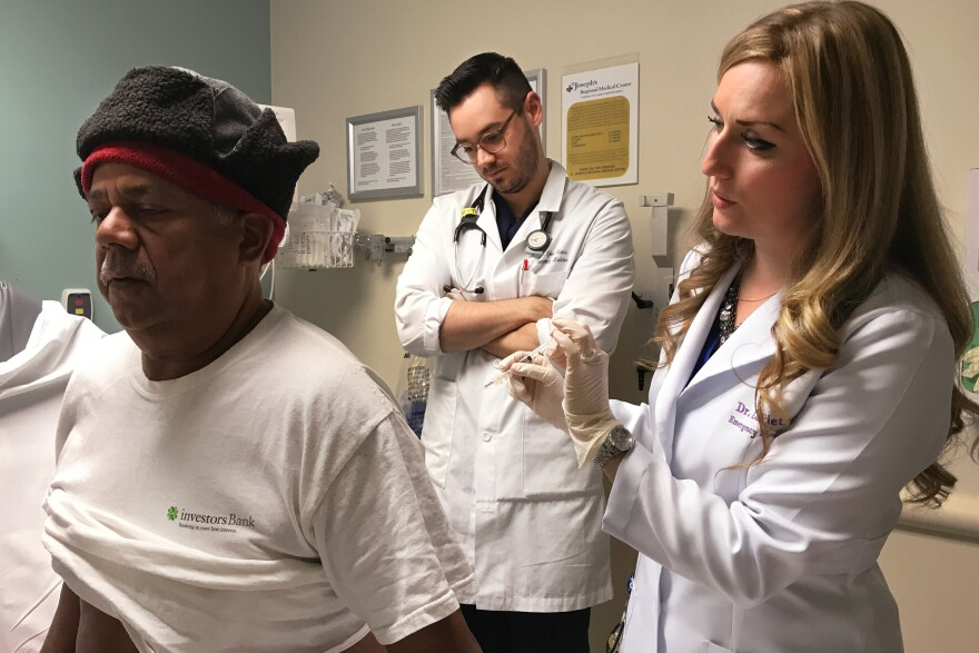 Francisco Hidalgo prepares to receive a trigger point injection from Dr. Alexis LaPietra (right) at St. Joseph's University Medical Center in Paterson, N.J., while Dr. Tyler Manis observes. An alternative to opioids, the trigger point injection involves dry needling to stop pain from a muscle spasm and a shot of local anesthetic for the soreness from the needle.