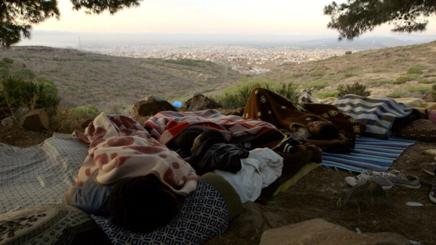 "Moneba (left) sleeps beside fellow migrants he calls his ""brothers"" in a hidden forest camp in Morocco. He was the chief of about 100 boys and young men from Guinea who hoped to reach Europe. The Spanish enclave of Melilla and the Mediterranean Sea are both visible in the distance."