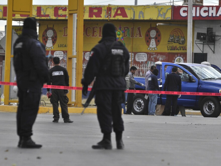 Federal police patrol a scene where two investigative police officers were shot by unidentified assailants in Juarez in December.