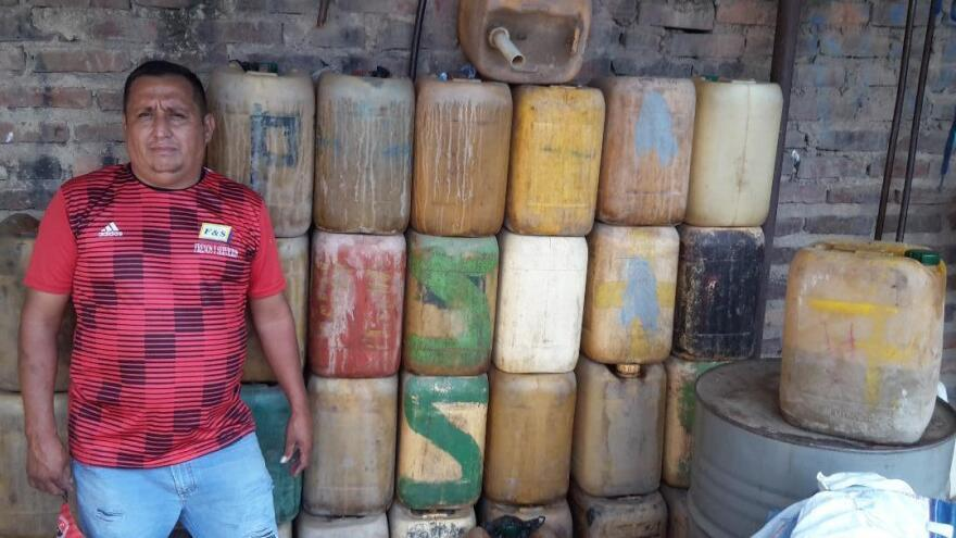 Álvaro Albarracín stands beside jugs used to smuggle gasoline from Venezuela into Colombia. He's pictured at a warehouse in Cúcuta he built after a fire destroyed his old one.