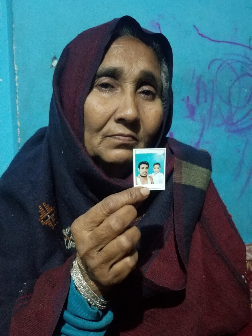 Nafisa, who goes by one name, holds a photo of her son Mohammed Mohsin with his son, now four years old. Mohsin was shot dead last month outside the family's home in Meerut.
