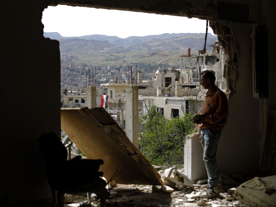 A man looks out of a damaged building in the mountain resort town of Zabadani, Syria, in the Damascus countryside, in May. The U.S. and Russia announced a new cease-fire deal on Friday.