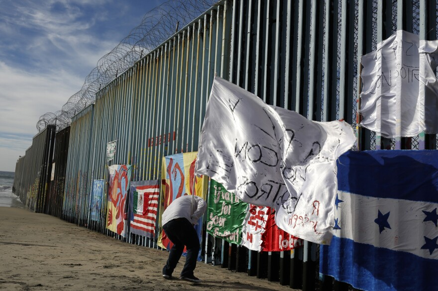"""Joseph, an migrant from Honduras, plants a white flag with the words, """"peace and God with us,"""" in front of the border wall during an art display on the border wall, topped with razor wire, Tuesday, Jan. 8, 2019, on the beach in Tijuana, Mexico. (Gregory Bull/AP)"""