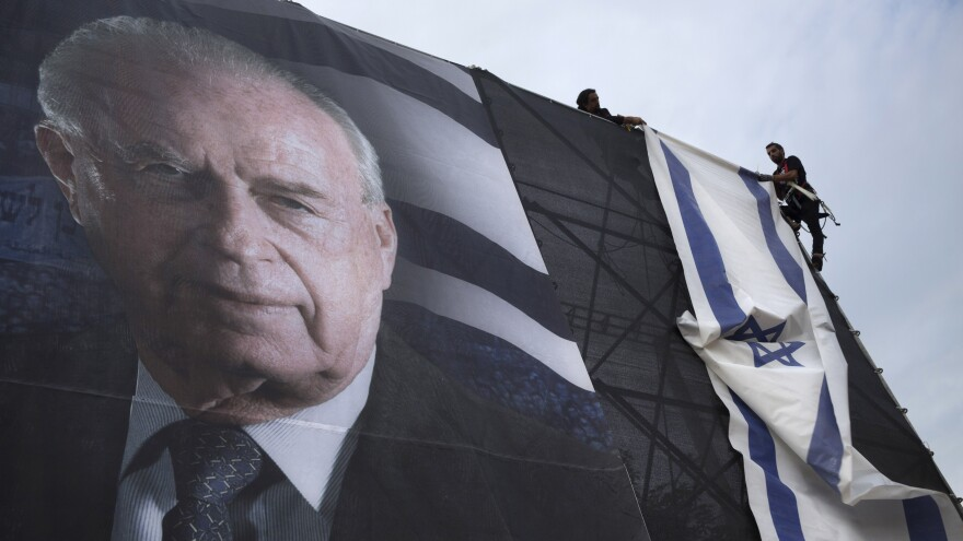 Israeli workers hang a billboard of Yitzhak Rabin ahead of a rally marking the 20th anniversary of his assassination, in Tel Aviv, on Oct. 28.