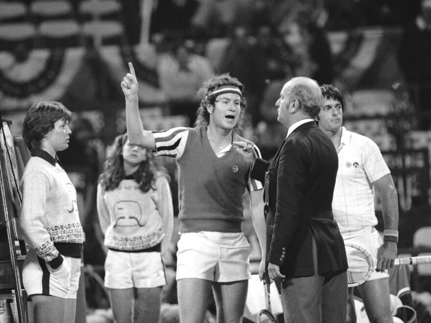 John McEnroe, known for his short temper, gestures angrily at umpire Joey Lessing during a match in New York in May 1980.