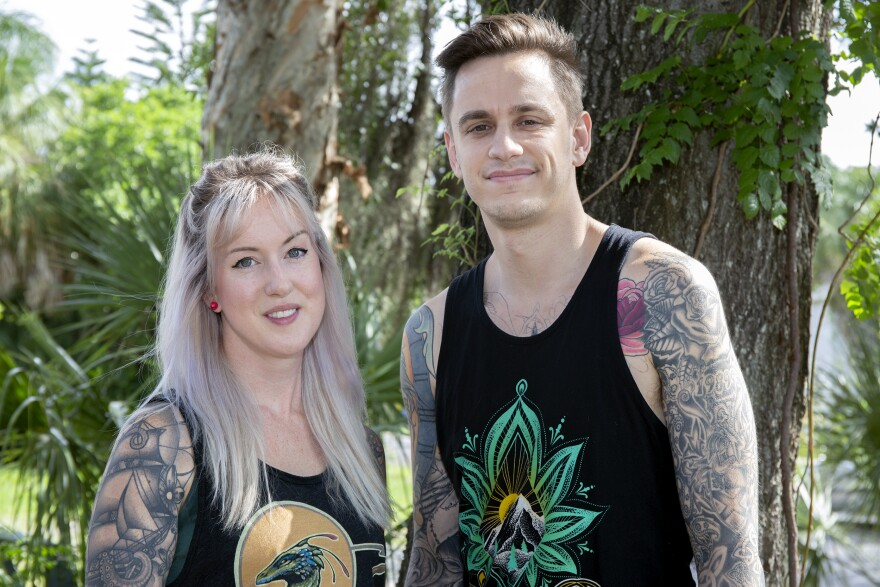 A tattooed couple stands in front of a tree.