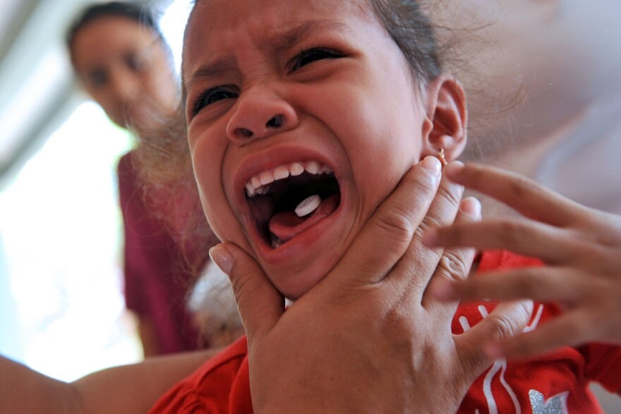 A girl cries while receiving a deworming pill in Managua, part of a campaign by the Nicaraguan Ministry of Health.
