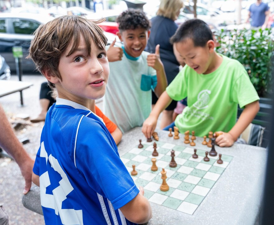 Kids enjoying a game of chess in front of the St. Louis Chess Club during the 2019 Sinquefield Cup