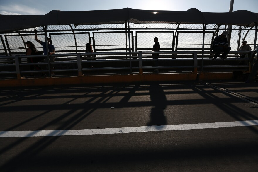 Pedestrians return to Ciudad Juarez, Mexico, as they cross the Paso del Norte bridge and leave El Paso, Texas, on Aug. 6, 2019. The Trump administration's policy forces asylum seekers to wait for their immigration court hearings in Mexico.