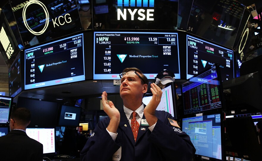 "A trader claps on the floor of the New York Stock Exchange at the close of the day after trading was paused for nearly four hours due to a ""technical glitch"" on Wednesday."