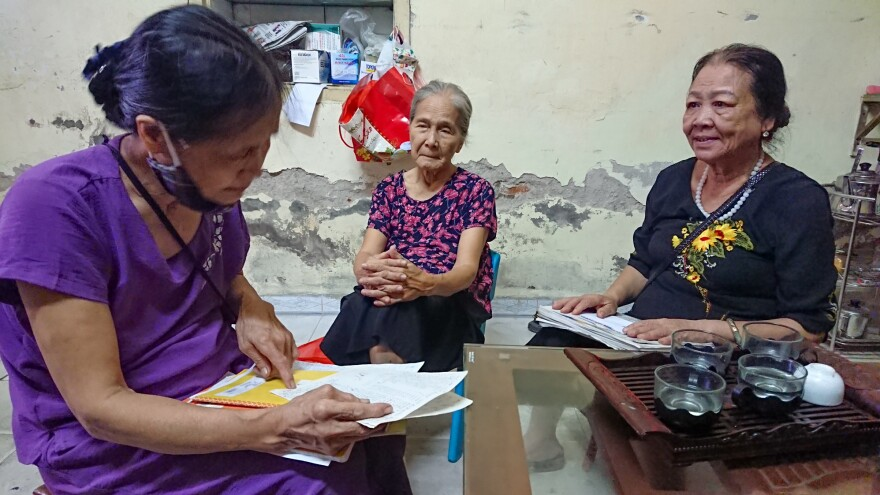 Dao Thi Hoa, right, chairwoman of the Intergenerational Self Help Club in the Khuong Din ward of Hanoi in Vietnam, checks the club's account book with other members.