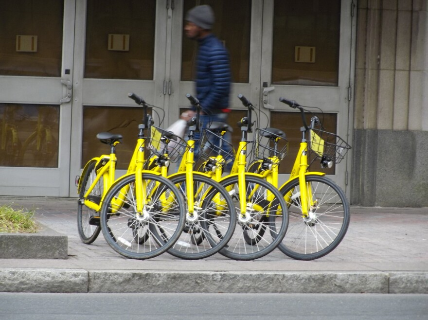 Rental bikes are lined up in front of an apartment building on North Tryon Street.