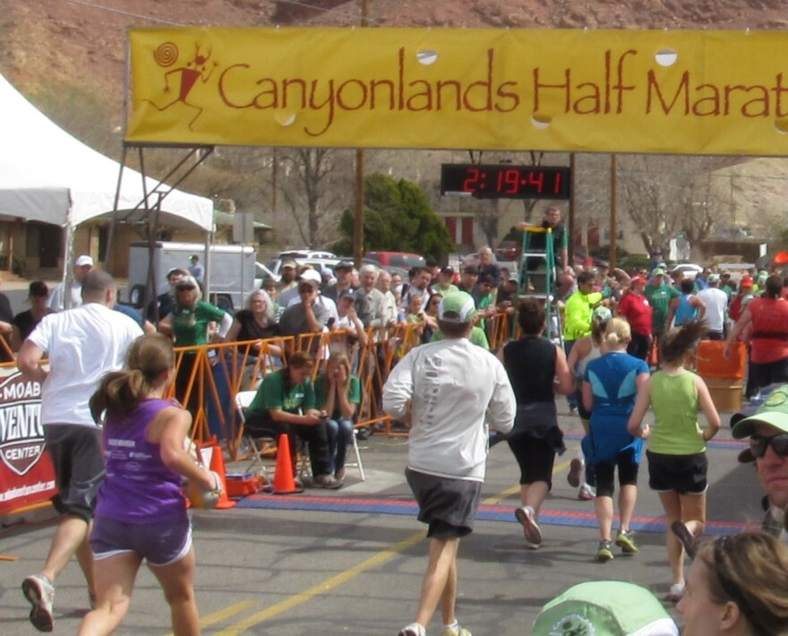 Photo of runners crossing a finish line with the sign Canyonlands Half Marathon against a red rock background.