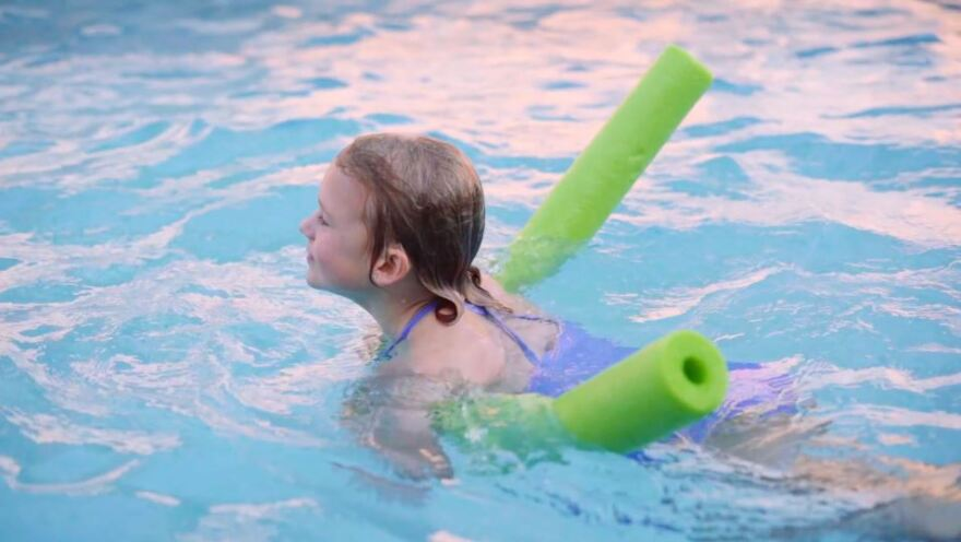 A little girl uses a swimming noodle to float in a scene from the FWDPC's YouTube video.