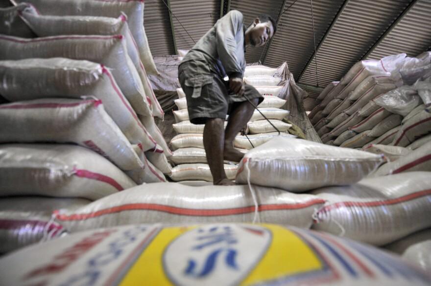 A laborer arranges sacks of rice at a market in Jakarta.