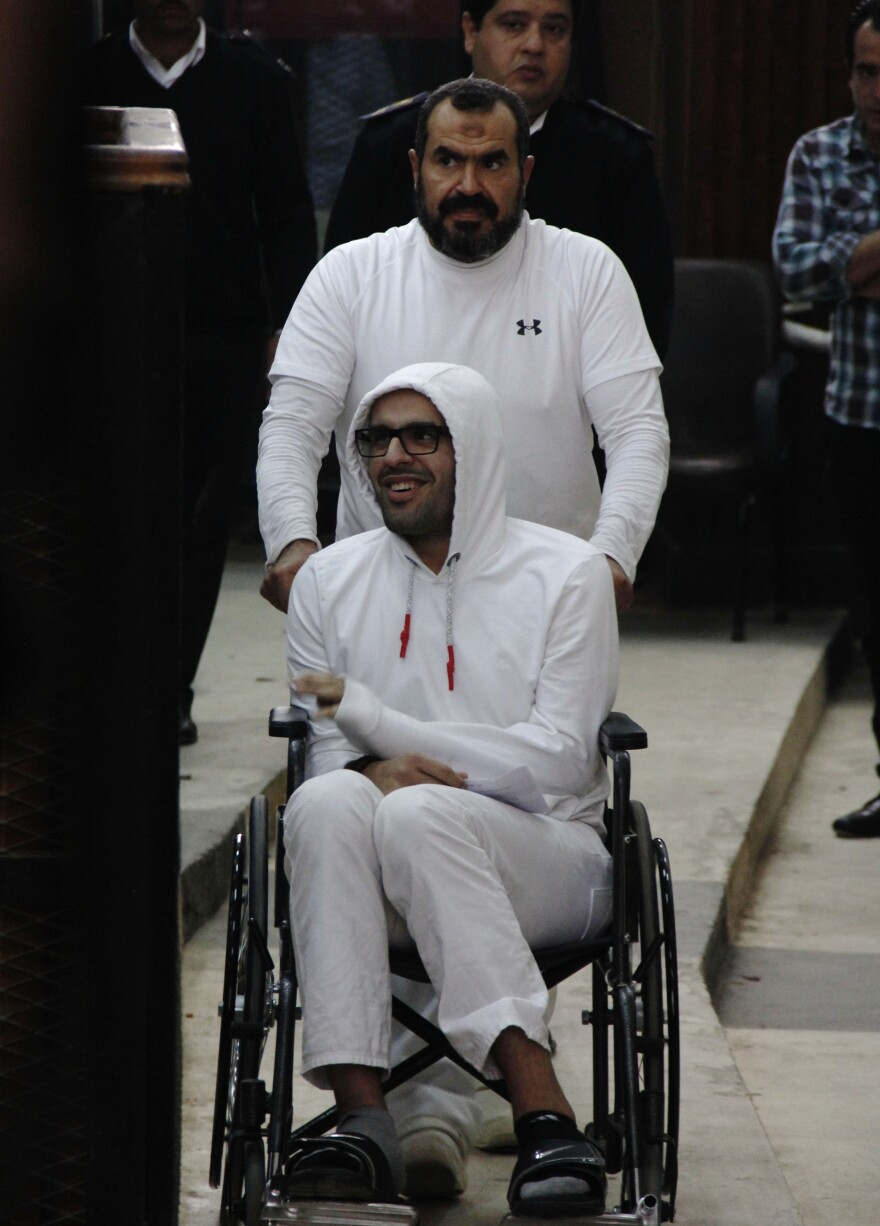 """In this March 2015, photo, Mohamed Soltan is pushed by his father Salah during a court appearance in Cairo. Egyptian officials freed Soltan May 30, 2015. He had been sentenced to life in prison on charges of financing an anti-government sit-in and spreading """"false news."""""""