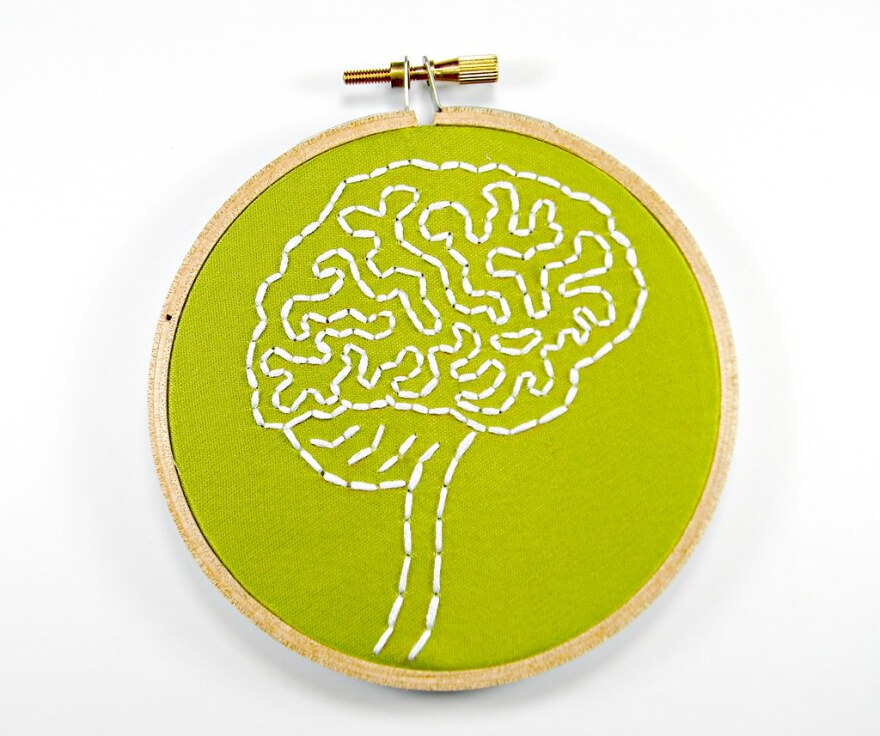 An embroidery hoop holds green fabric stitched with the outline of the folds of the brain.