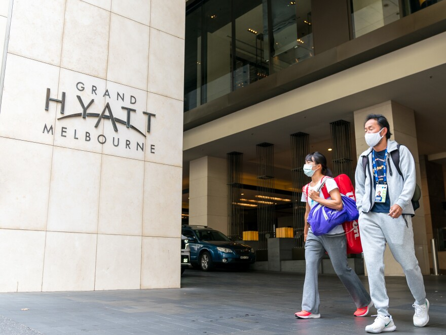 Players and their entourages emerge from the Grand Hyatt Melbourne on Thursday. A positive case was discovered at one of the Australian Open quarantine hotels, with some 500 Australian Open players, officials and support staff told to quarantine and get tested.