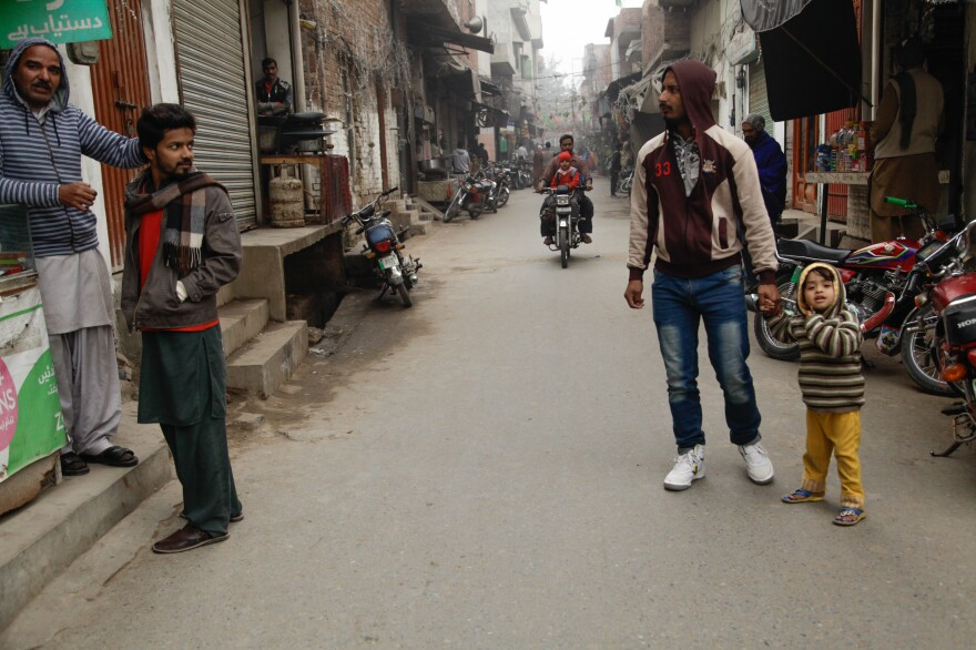 An adult escorts a child in Kasur. Residents say they fear letting their children go out alone.