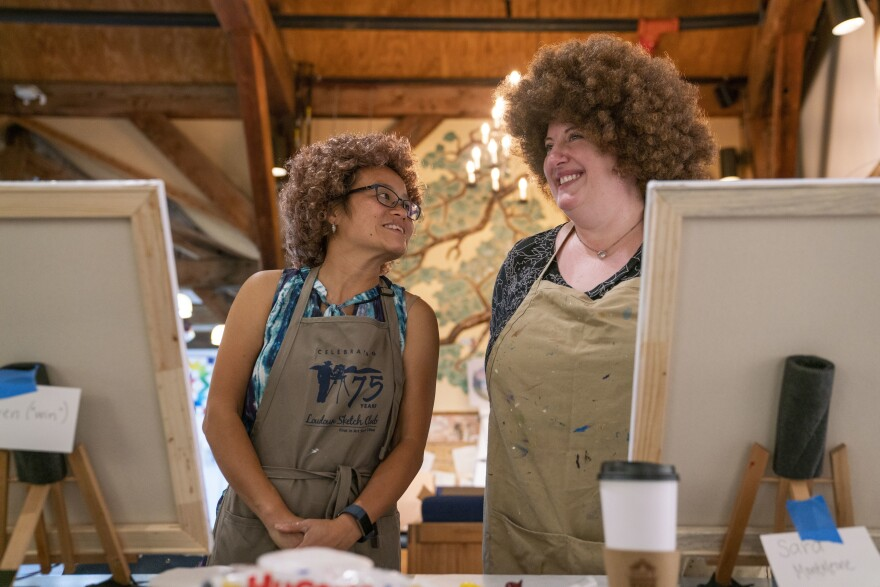 From left, Huyen MacMichael and Sara Monteleone exchange laughs during the  Bob Ross painting class at the Franklin Park Arts Center. MacMichael and Monteleone wore the iconic Bob Ross wig during the entire class.