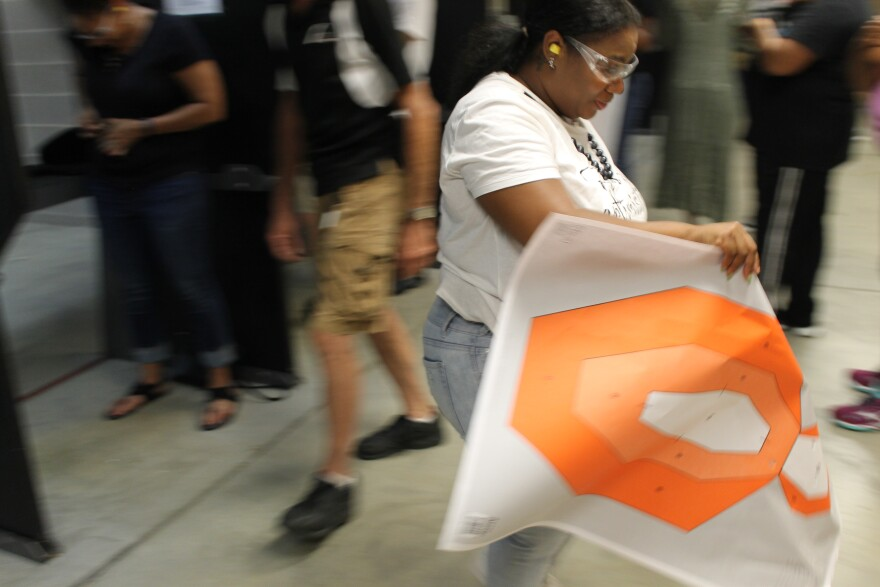 One woman who attended the ladies night event walks away from her lane carrying her paper target practice sheet.