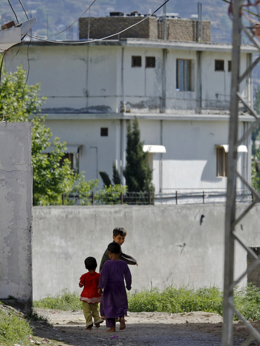 """Children walk past the house of former al-Qaida leader Osama bin Laden in Abbottabad, Pakistan, on May 8, 2011. A new Pakistani report says the """"extent of incompetence"""" in failing to detect bin Laden despite the size of the house was """"to put it mildly ... astounding, if not unbelievable."""""""