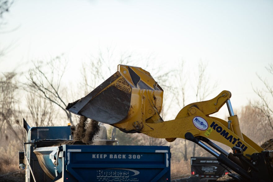 A yellow bulldozer drops a load of shingles into a truck. It's 8 a.m. and a cold day in North Texas. Construction workers wear thick jackets and begin the process of removing Shingle Mountain from the Floral Farms community.