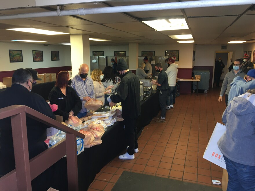 A photo of volunteers getting grab-and-go bags ready for homeless people.