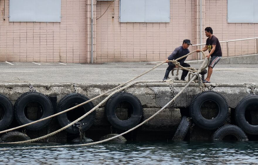 Workers secure a rope to the shore at the Patoutzu Fishing Harbour in Keelung on Tuesday, as boats come into dock ahead of the arrival of Typhoon Maria.