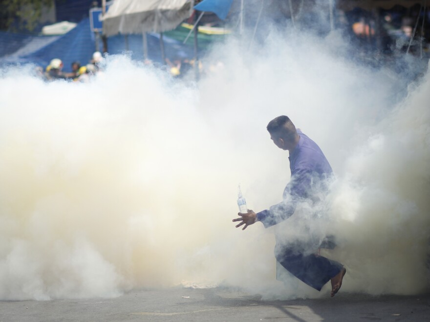 An anti-government protester is caught in tear gas during clashes with riot police in Bangkok, Thailand, on Tuesday.