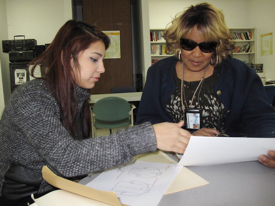 Fashion Institute of Technology student Erika Morales (left) discusses clothing designs with VA patient Anna Smith, an Air Force veteran who wears a back brace and uses a wheelchair and cane.