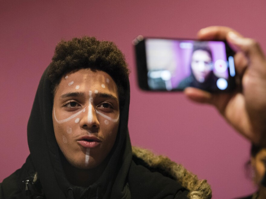 Jayden Pontes, 17, a student from Boston Arts Academy, is filmed wearing face paint similar to characters from <em>Black Panther</em> during a discussion of the significance of the film's release in Boston on Wednesday. The students planned to wear the face paint to the film's screenings.